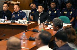 Philippine Police Chief Ronald Dela Rosa, second from left, looks at former Filipino militiaman Edgar Matobato during his testimony at the Philippine Senate in Pasay, south of Manila, Philippines on Thursday, Sept. 15, 2016. Matobato said that Philippine President Rodrigo Duterte, when he was still a city mayor, ordered him and other members of a squad to kill criminals and opponents in gangland-style assaults that left about 1,000 dead. (AP Photo/Aaron Favila)