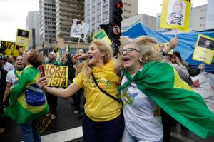 People celebrate the impeachment of Brazil's President Dilma Rousseff in Sao Paulo, Brazil, Wednesday, Aug. 31, 2016. Brazil's Senate on Wednesday voted to permanently remove Rousseff from office 61-20, more than the 54 votes they needed. (AP Photo/Andre Penner)