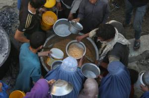 In this Thursday, June 9, 2016 photo, Afghan women and children receive free food donated by other villagers as they prepare to break their fast during the holy month of Ramadan in Kabul, Afghanistan. Fifteen years ago as the United States prepared to invade Taliban-ruled Afghanistan, then-First Lady Laura Bush took over her husband's weekly radio address to tell the American people that part of the reason for going to war after the attacks of September 11, 2001, was to liberate Afghan women from the brutality of the extremists' regime. But abuse of women in Afghanistan remains entrenched and endemic, despite constitutional guarantees of equality.(AP Photo/Rahmat Gul)