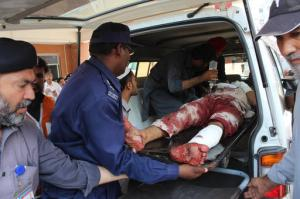 Pakistani volunteers carry an injured person who arrived from Mardan, at a local hospital in Peshawar, Pakistan, Friday, Sept. 2, 2016. Northwestern Pakistan was struck by two separate militant attacks on Friday, when gunmen wearing suicide vests stormed a Christian colony near the town of Peshawar, killing one civilian, and a suicide bomb attack on a district court in the town of Mardan killed scores of people and wounded many. (AP Photo/Mohammad Sajjad)