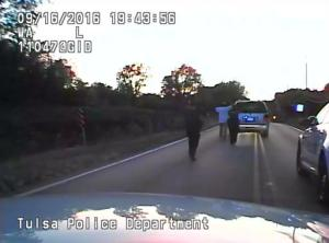 In this image made from a Friday, Sept. 16, 2016 police video, Terence Crutcher, center, is pursued by police officers as he walk to an SUV in Tulsa, Okla. Crutcher was taken to the hospital where he was pronounced dead after he was shot by the officer around 8 p.m., Friday, police said. Crutcher had no weapon on him or in his SUV, Tulsa Police Chief Chuck Jordan said Monday, Sept. 19, 2016. (Tulsa Police Department via AP)