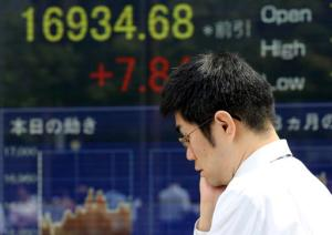A man walks by an electronic stock board of a securities firm in Tokyo, Friday, Sept. 2, 2016. Most Asian markets were listless Friday as investors awaited key U.S. job data that could influence the Fed's interest rate policy. (AP Photo/Koji Sasahara)