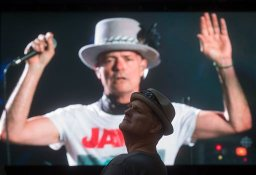 """Lead singer Gord Downie is seen performing on a screen as a man watches during a viewing party for the final stop in Kingston, Ontario, from Vancouver, British Columbia, Saturday Aug. 20, 2016. The Tragically Hip mixed fan favourites, newer songs and some politics on Saturday night during the final show of their """"Man Machine Poem"""" tour. (Darryl Dyck/The Canadian Press via AP)"""