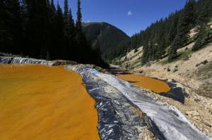 FILE - In this Aug. 14, 2015, file photo, water flows through a series of sediment retention ponds built to reduce heavy metal and chemical contaminants from the Gold King Mine wastewater accident, in the spillway about 1/4 mile downstream from the mine, outside Silverton, Colo. The mine that spilled 3 million gallons of contaminated wastewater into rivers in three Western states has been designated a Superfund site. The U.S. Environmental Protection Agency's action Wednesday, Sept. 7, 2016, clears the way for a multimillion-dollar federal cleanup of the Gold King Mine and 47 other nearby mining-related sites. (AP Photo/Brennan Linsley, File)
