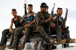 Rebels of the Revolutionary Armed Forces of Colombia, FARC, arrive on top of a truck to El Diamante, in southern Colombia, Friday, Sept. 16, 2016. FARC rebels are gathering for a congress to discuss and vote a peace accord reached with the Colombian government to end five decades of war. Historically secretive, this congress is the first one open to civilians. (AP Photo/Ricardo Mazalan)