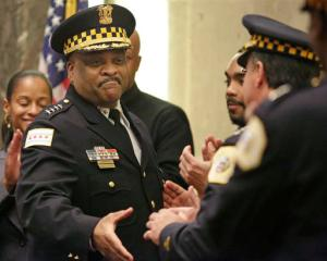FILE - In this April 13, 2016 file photo, Chicago's police superintendent Eddie Johnson, left, shakes hands with other officers at a city council meeting in Chicago. The Chicago Police Department plans to hire more than 500 additional officers as it struggles to deal with a violent year full of killings and gun crimes, a city official told The Associated Press on Tuesday Sept. 20, 2016. Chicago Police Superintendent Eddie Johnson will announce the hires Wednesday, according to the official. (AP Photo/M. Spencer Green File)