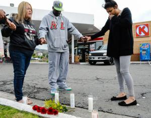 FILE - In this March 14, 2016 file photo, Francine Prieto-Estrada, left, leads Donald Pride and Elisa Castro in a prayer at memorial site for 12-year-old shooting victim Jason Spears at a Circle K in San Bernardino, Calif. His 14-year-old cousin, Terrance Spears, was wounded as the pair walked to the convenience store. San Bernardino has seen a rise in homicides, and Police Chief Jarrod Burguan said homicides could double in 2016 from last year. (Rachel Luna/The Sun via AP, File)