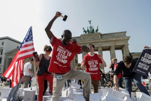 Protestors are tearing down a so called 'Trump's wall of hate' as part of a demonstration against Republican presidential candidate Donald Trump in front of the Brandenburg Gate at the Pariser Platz in Berlin, Germany, Friday, Sept. 23, 2016. (AP Photo/Markus Schreiber)