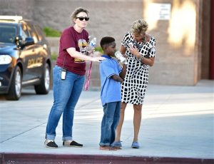 A shoeless student stands with school administrators waiting to be picked up after being released from Walter Johnson Junior High School Wednesday, Sept. 7, 2016, in Las Vegas. Hundreds of anxious parents staked out a Las Vegas middle school after mercury was found and federal officials kept more than a thousand students for up to 17 hours to screen them for exposure to the neurotoxin.. (David Becker/Las Vegas Review-Journal via AP)