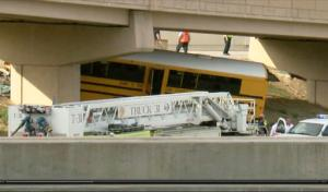In this image made from video provided by KMGH/THEDENVERCHANNEL.COM, emergency personnel stand near the scene of a school bus that crashed into a concrete pillar in Denver,  Sunday, Sept. 11, 2016. The school bus driver was killed Sunday and several others were seriously injured after the bus veered off a roadway at Denver International Airport and crashed into a concrete pillar, police said. (KMGH/THEDENVERCHANNEL.COM via AP)