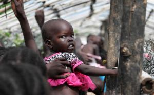 "FILE - In this Monday, July 25, 2016 file photo, a baby is lifted up as people queue for food distribution in a camp for the displaced at the United Nations base in Juba, South Sudan. The United Nations said Friday, Sept. 9, 2016 that hunger in South Sudan has reached ""unprecedented"" levels, with nearly 5 million people suffering from severe food insecurity. (AP Photo/Justin Lynch, File)"