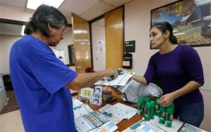 A community worker at the Wynwood Community Service Center, right, hands out to a local resident a can of insect repellent Thursday, Aug. 4, 2016, in Miami. The CDC has warned expectant mothers to steer clear of the city's Wynwood neighborhood, where over a dozen people are believed to have been infected with the Zika virus through mosquito bites in the first such cases on record in the mainland U.S. (AP Photo/Alan Diaz)