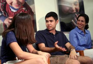 In this July 7, 2016, photo, Evee Bak, left, talks with her brother Tom Bak, center, while their mother, Erin Lopes, looks on at the Seaver Autism Center at Mount Sinai Hospital in New York. Autism is at least four times more common in boys, and Tom is affected, while Evee isn't. The gender effect is a hot topic in autism research and one that could lead to new ways of diagnosing and treating the condition. (AP Photo/Seth Wenig)