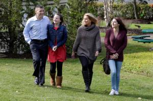 From left, Peter Foster; adopted daughter; Kerry, 12; his wife, Susan, and their biological daughter, Emma, 17, walk on the grounds outside St. Barnabas Hospital, in Livingston, N.J., Tuesday, Oct. 25, 2016. More than 15 years ago, 17 babies, including Emma, were born after an experimental infertility treatment that gave them DNA from three people: Mom, Dad and an egg donor. Now researchers have checked up on how the babies are doing as teenagers. The preliminary verdict: The kids are all right. (AP Photo/Richard Drew)