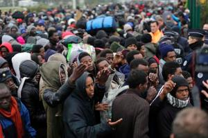 "Migrants line-up to register at a processing centre in the makeshift migrant camp known as ""the jungle"" near Calais, northern France, Monday Oct. 24, 2016. French authorities are beginning a complex operation, unprecedented in Europe, to shut down the makeshift camp, uprooting thousands who made treacherous journeys to escape wars, dictators or grinding poverty and dreamed of making a life in Britain. (AP Photo/Emilio Morenatti)"