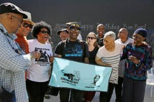 In this photo taken Saturday, Oct. 8, 2016, former members of the Black Panther Party laugh and visit outside a museum after an anniversary meeting in Oakland, Calif. In the front row is Billy X. Jennings, center, M. Gayle Asali-Dickson, second from right and Lorene Johnson, right. Hundreds of former Black Panthers from around the world are expected to gather in Oakland, Calif., for a four-day conference that started Thursday, Oct. 20, 2016. The Panthers emerged from the gritty city 50 years ago, declaring a new party dedicated to defending African-Americans against police brutality and protecting their rights. (AP Photo/Eric Risberg)