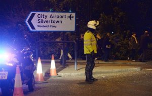 """A policeman stands outside London City Airport which has been closed as dozens of passengers have been treated for breathing difficulties after what the emergency services called a reported """"chemical incident."""", Friday, Oct. 21, 2016. The airport said passengers were told to leave the terminal Friday afternoon because a fire alarm was sounding. Departing flights were suspended, and several incoming flights diverted to other airports. (Victoria Jones/PA via AP)"""