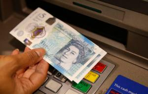 FILE - In this Sept. 13, 2016 file photo, a member of staff at a branch of Halifax bank, in London, displays a new British 5 pound sterling note, made from polymer, which is being launched Tuesday.  The beleaguered British pound plummeted briefly to a fresh 31-year low Friday, Oct. 7, 2016,  amid intensifying concerns about Britain's exit from the European Union. The pound tumbled nearly 6 percent in early Asian trading, falling as low as $1.1789, according to FactSet data.  (AP Photo/Alastair Grant, File)