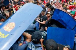 In this Wednesday, Oct. 19, 2016 photo, police and protesters clash during a violent protest outside the U.S. Embassy in Manila, Philippines. A Philippine police van rammed into protesters, leaving several bloodied, as an anti-U.S. rally turned violent Wednesday at the embassy in Manila. (AP Photo/Bullit Marquez, File)