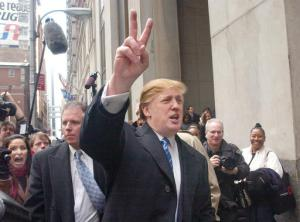 """FILE - In this March 18, 2004 file photo, developer Donald Trump signals to those waiting in line at a casting call for the second season of his television show, """"The Apprentice,"""" in New York. Trump is surging back into the public consciousness on a wave of publicity from his reality show and back onto the A-list again. Trump once claimed to be publicity shy, no joke. It's right there in The New York Times of Nov. 1, 1976. In the same article, the 30-year-old real estate developer talks up his millions, showcases his penthouse apartment and Cadillac, and allows a reporter to tag along as he visits job sites and lunches at the """"21"""" club before hopping an evening flight to California for more deal-making. So much for that shy-guy claim.(AP Photo/Frank Franklin II, File)"""