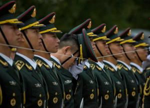 In this Thursday, Oct. 20, 2016 photo, a member of a Chinese honor guard adjusts his cap as they line up with the help of a string before a welcome ceremony for Philippine President Rodrigo Duterte outside the Great Hall of the People in Beijing. (AP Photo/Ng Han Guan, File)
