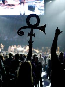 A Prince fan holds up his symbol Thursday, Oct. 13, 2016 in St. Paul, Minn., during a tribute concert honoring the late musician who died in April (AP Photo/Jim Mone)