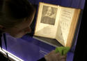 """In this Tuesday, Oct. 11, 2016 photo book conservator Lauren Schott polishes a case containing 17th century editions of plays attributed to William Shakespeare in an exhibit called """"Shakespeare Unauthorized"""" at the Boston Public Library, in Boston. The public is to get a rare glimpse of first and early editions of some of Shakespeare's most beloved plays, including """"A Midsummer Night's Dream,"""" Hamlet"""" and """"The Merchant of Venice"""" in the exhibit which opens Friday, Oct. 14 and is to run through March 31 at the library. (AP Photo/Steven Senne)"""