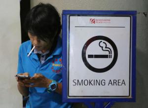 A Filipino smokes by a smoking area sign outside a mall in Manila, Philippines Tuesday, Oct. 11, 2016. Health Secretary Paulyn Ubial said Tuesday she hopes Philippine President Rodrigo Duterte can sign the draft executive order banning smoking in public nationwide before the end of the month. She also said e-cigarettes will be included in the ban. (AP Photo/Aaron Favila)