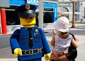 An actor dressed as a Lego police officer mini-figure greets a child at Legoland Dubai, in Dubai, United Arab Emirates, Monday, Oct. 31, 2016. The Legoland park, part of the larger Dubai Parks & Resorts project, is the first among its planned attractions to opens. (AP Photo/Jon Gambrell)