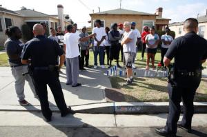 Los Angeles Police officers speak to neighbors and members of the community gathered around a makeshift memorial outside a residence on Sunday, Oct. 2, 2016. Officers shot and killed Carnell Snell Jr. in south Los Angeles on Saturday at the end of a car chase, sparking a protest by several dozen people angered by another fatal police shooting of a black man. (AP Photo/Damian Dovarganes)