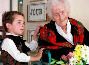 FILE - In this Feb. 12, 1997 file photo shows Thomas, 5, looks at Jeanne Calment after he brought her flowers at her retirement home in Arles, southern France. Calment, believed to be the world's oldest person, died at the age of 122 in 1997. New research published in the journal Nature on Wednesday, Oct. 5, 2016 suggests there's a limit to our life span and that the odds of breaking Calment's record are small. (AP Photo/Florian Launette,File)