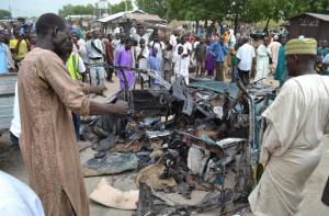 People gather at the scene of a car bomb explosion in Maiduguri, Nigeria, Wednesday, Oct. 12, 2016.  The explosion seemed to target a taxi filled with passengers in northeast Nigeria on Wednesday, in the deadliest bombing to hit the area's largest city in several months, officials and witnesses said. (AP Photo/Jossy Ola)