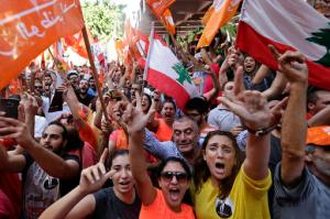 Supporters of Christian leader Michel Aoun, holding Free Patriotic Movement and Lebanese flags, celebrate the election of the new President Michel Aoun, in Beirut, Lebanon, Monday, Oct. 31, 2016. Lebanon's parliament on Monday elected Michel Aoun, an 81-year-old former army commander and strong ally of the militant group Hezbollah, as the country's president, ending a more than two-year vacuum in the top post and a political crisis that brought state institutions perilously close to collapse. (AP Photo/Hassan Ammar)
