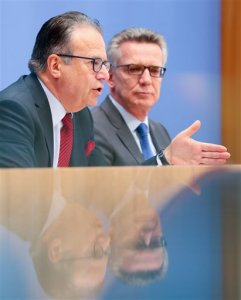 Federal Minister of the Interior Thomas de Maiziere and head of the Federal Agency of Migration and Refugees Frank-Juergen Weise hold a press conference regarding the numbers of asylum seeker for September 2016 as well as the third quarter 2016 in the Federal press conference in Berlin, Germany, Oct. 12, 2016. (Kay Nietfeld/dpa via AP)