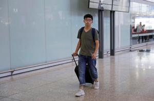 Hong Kong pro-democracy activist Joshua Wong, center, arrives at Hong Kong airport from Bangkok, Wednesday, Oct. 5, 2016. Thailand stopped the teen pro-democracy activist from entering the country and sent him back to Hong Kong, officials said Wednesday, in a move supporters suspected was triggered by pressure from Beijing. (AP Photo/Kin Cheung)
