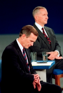 FILE - In this Oct. 15, 1992, file photo President George H.W. Bush looks at his watch during the 1992 presidential campaign debate with other candidates, Independent Ross Perot, top, and Democrat Bill Clinton, at the University of Richmond, Va. For presidential candidates, the town hall debate is a test of stagecraft as much as substance. When Hillary Clinton and Donald Trump meet in the Sunday, Oct.9, 2016, contest, they'll be fielding questions from undecided voters seated nearby. In an added dose of unpredictability, the format allows the candidates to move around the stage, putting them in unusually close proximity to each other. (AP Photo/Ron Edmonds, File)