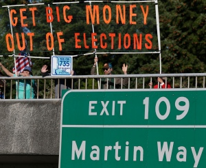 FILE - In this Sept. 22, 2016, file photo, supporters of Initiative 735 hold a banner above the I-5 freeway during the evening commute in Lacey, Wash.  Voters are disgusted with the way campaigns are paid for _ disproportionately by big-money donors, including those who stand to gain or lose from government decisions. The rules even allow donors to hide their identities by giving to groups that can weigh in on the election without having to file detailed public paperwork about their finances. The system leaves everyday Americans fearing their voices are being drowned out by these moneyed interests. (AP Photo/Ted S. Warren, File)