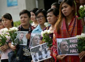 Supporters hold flowers and and placards as the British human rights activist Andy Hall arrives at Bangkok South Criminal Court for his verdict on criminal and civil defamation cases filed against him, in Bangkok, Thailand Tuesday, Sept. 20, 2016. Bangkok South Criminal Court found Hall guilty Tuesday of criminal defamation against Natural Fruit Company Ltd. in connection with a report he researched for the Finnish consumer agency Finnwatch that alleged labor abuses at the company's facilities. (AP Photo/Sakchai Lalit)
