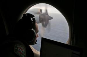 FILE - In this March 22, 2014 file photo, flight officer Rayan Gharazeddine scans the water in the southern Indian Ocean off Australia from a Royal Australian Air Force AP-3C Orion during a search for the missing Malaysia Airlines Flight MH370. A ship involved with the deep-sea sonar search for missing Malaysia Airlines Flight 370 is being fitted with equipment to examine several sonar contacts of interest on the remote seabed west of Australia, the Australian Transport Safety Bureau said on Wednesday, Oct. 19, 2016. (AP Photo/Rob Griffith, File)