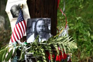 FILE – In this July 29, 2015, file photo, photos of Sam DuBose hang on a pole at a memorial near where he was shot and killed by a University of Cincinnati police officer during a July 19, 2015, traffic stop in Cincinnati. Former University of Cincinnati police officer Ray Tensing, facing trial on charges of murder and voluntary manslaughter, was due back in court for a Friday, Oct. 14, 2016, pretrial hearing, ahead of the planned start of jury selection on Oct. 25, 2016. (AP Photo/Tom Uhlman, File)