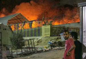 Migrants watch a large fire as it burns inside the Moria refugee camp on the northeastern Greek island of Lesbos, late Monday, Sept. 19. 2016. Greek police say a large fire has swept through a big camp for refugees and other migrants on the eastern Aegean island of Lesbos, forcing its evacuation. None of the more than 4,000 people in the Moria camp was reported injured in Monday's blaze, which damaged tents and prefabricated housing units. (AP Photo/Michael Schwarz)