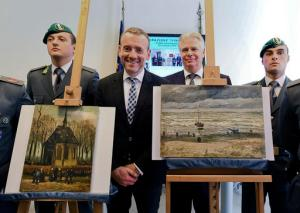 Director of Amsterdam's Van Gogh Museum Axel Rueger, center, stands next to the paintings Congregation Leaving The Reformed Church of Nuenen, left, and 1882 Seascape at Scheveningen by Vincent Van Gogh, during a press conference in Naples, Italy, Friday, Sept. 30, 2016. The paintings which had been stolen in an Amsterdam museum in 2002, were recovered by Naples investigators among the assets of a Camorra group. (Ciro Fusco/ANSA via AP)