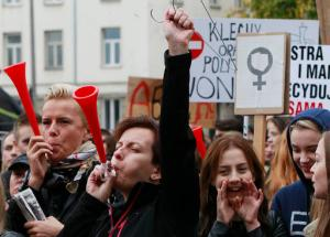 "Polish women and some male supporters blow horns while raising a hanger, the symbol of illegal abortion, during a nationwide strike and demonstration to protest a legislative proposal for a total ban on abortion in Warsaw, Poland, Monday, Oct. 3, 2016. Polish women are waging a nationwide strike to protest a legislative proposal for a total ban on abortion, with workers and students boycotting their jobs and classes and housewives refusing to do housework. Some businesses and restaurants are also closed on what is being called ""Black Monday,"" an expression of outrage against a proposal to further restrict an abortion law that is already one of the most limited in Europe. (AP Photo/Czarek Sokolowski)"