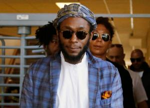 FILE - In this March 24, 2016 file photo, American actor and musician Yasiin Bey, also known as Mos Def, leaves the Bellville Magistrates' Court in Bellville, South Africa. Bey left South Africa on Tuesday Nov. 22, 2016, after apologizing to the government after authorities accused him of violating the country's immigration laws. In turn, authorities say, charges against him will be dropped. (AP Photo/Schalk van Zuydam, File)