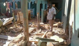 A man stands amid the debris at the scene of an attack in the town of Mandera, Kenya, near the border with Somalia, Tuesday, Oct. 25, 2016. A Kenyan official says a number of people were killed in the extremist attack and that gunmen from the Somalia-based extremist group al-Shabab are suspected of carrying out the attack. (AP Photo)