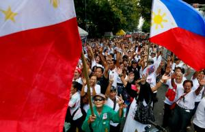"""Supporters of the late Philippine dictator Ferdinand Marcos cheer after the Philippine Supreme Court voted 9-5 with one abstention to rule that Marcos can be buried at the heroes' cemetery in a ruling opponents say rolled back the country's democratic triumph when Filipinos ousted the strongman in a 1986 """"people power"""" revolt Tuesday, Nov.8, 2016 in Manila, Philippines. Court spokesman Theodore Te says the 15-member court voted 9-5 with one abstention Tuesday to dismiss petitions opposing President Rodrigo Duterte's approval of Marcos's burial at the cemetery. (AP Photo/Bullit Marquez)"""