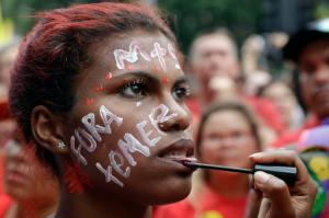 "A demonstrator with the Portuguese words ""Temer out"" holds still for someone else applying lip gloss during protest demanding the impeachment of Brazil's President Michel Temer in Sao Paulo, Brazil, Sunday, Nov. 27, 2016. Protesters expressed outrage at a host of Temer's policies, including the government's proposal to cap spending to rein in the deficit. (AP Photo/Andre Penner)"