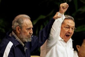 FILE - In this April 19, 2011 file photo, Fidel Castro, left, raises his brother's hand, Cuba's President Raul Castro, center, as they sing the anthem of international socialism during the 6th Communist Party Congress in Havana, Cuba. Cuban President Raul Castro has announced the death of his brother Fidel Castro at age 90 on Cuban state media on Friday, Nov. 25, 2016.(AP Photo/Javier Galeano, File)
