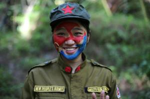 In this photo taken Nov. 23, 2016, a 24-year-old New People's Army guerrilla, who uses the nom de guerre Comrade Katryn, smiles as she talks to reporters at a rebel encampment tucked in the harsh wilderness of the Sierra Madre mountains southeast of Manila, Philippines. Communist guerrillas warn that a peace deal with President Rodrigo Duterte's government is unlikely if he won't end the Philippines' treaty alliance with the United States and resist control by other countries. (AP Photo/Aaron Favila)