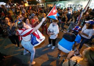 FILE- In this Nov. 26, 2016, file photo, members of the Cuban community dance in the street as they react to the death of Fidel Castro in front of the Versailles Restaurant in the Little Havana neighborhood of Miami. For the hundreds of thousands of children born of Cuban exiles, some who are two and three generations removed from the island, Fidel Castro's death potentially opens a door to a world previously off-limits. (AP Photo/Wilfredo Lee, File)
